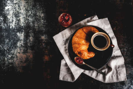Homemade continental breakfast, coffee with spice, cane sugar, croissants. jam on a black rusty metal table, copy space top view Archivio Fotografico