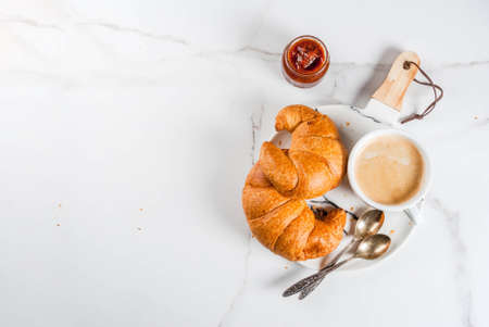 Homemade continental breakfast, coffee croissants. jam on white marble table, copy space top view