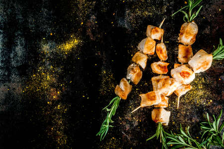 Grill, barbecue meat. Chicken skewers with rosemary. On a black rusty metallic background, copy space top view