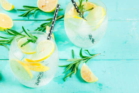Cold lemonade or alcohol vodka cocktail with lemon and rosemary, on light blue table, copy space Foto de archivo