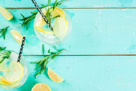 Limonade froide ou cocktail de vodka à l'alcool au citron et au romarin, sur table bleu clair, copie vue de dessus de l'espace