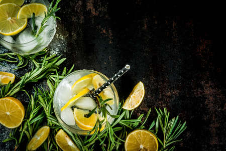 Cold lemonade or alcohol vodka cocktail with lemon and rosemary, On a black rusty metallic background, copy space top view