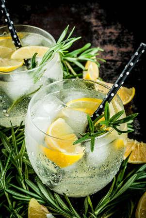 차가운 레모네이드 또는 알코올 보드카 칵테일 레몬와 로즈마리, 검은 녹슨 금속성 배경에 복사 공간