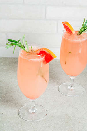 Festive drink for Christmas party, Mimosa cocktail with Champagne, Grapefruit and Rosemary, on stone tale, copy space Stock Photo