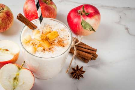 健康的なビーガンフード。食事の朝食や軽食。アップルパイスムージー、リンゴ、ヨーグルト、シナモン、スパイス、クルミ。ガラスの上に 白い大