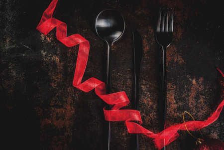Christmas, New Year celebration concept, set of silverware on a dark rusty background,decorated with red ribbon and christmas tree ball, top view copy space