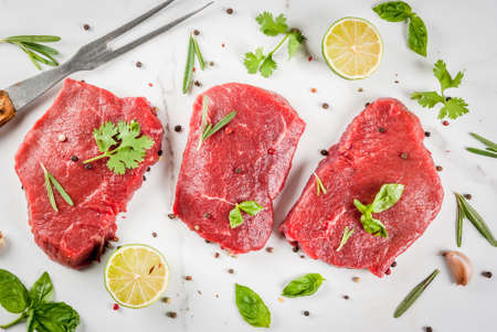 Fresh raw meat. Beef tenderloin, steaks, on a white marble table. With olive oil, spices for cooking - basil, rosemary, coriander, parsley, garlic, lemon, salt, pepper. Copy space top view Banco de Imagens