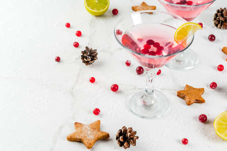 Fall and winter drinks. Christmas holiday beverage. Festive cranberry martini with lime. On white table with christmas decoration, copy space Stock Photo