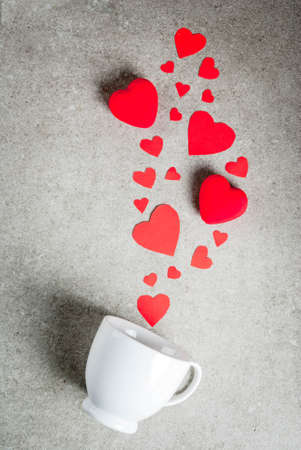 Romantic background, Valentine's day. A gray stone table with a cup for coffee or hot chocolate, decorated with paper and plush red hearts, top view flat lay, copy space 스톡 콘텐츠