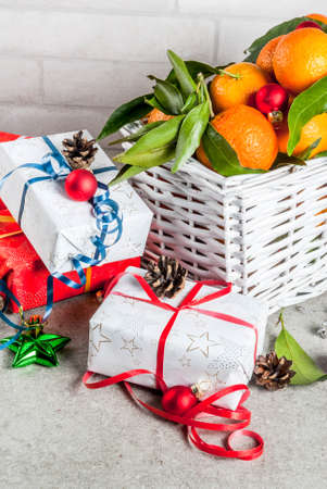 Christmas and New Year concept. Fresh Tangerines with green leaves in a white basket, Christmas decoration and gift boxes, on grey table, copy space