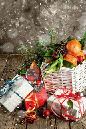 Christmas and New Year concept. Fresh Tangerines with green leaves in a white basket, Christmas decoration and gift boxes, on old rustic wooden table, copy space toned, with snow effect Stock Photo