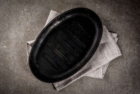 Grey stone culinary background with empty black pan, top view copy space Banco de Imagens