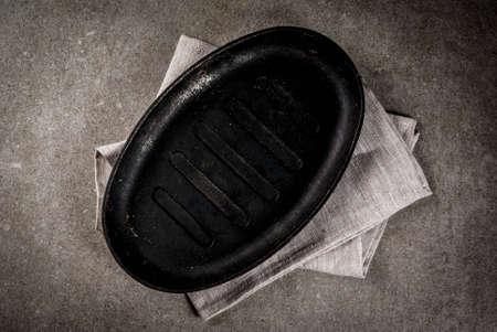 Grijze steen culinaire achtergrond met lege zwarte pan, de ruimte van het hoogste meningsexemplaar