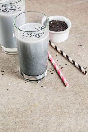 Trendy vegan food recipes, Black Sesame Iced Latte or smoothie with sesame seeds, dried coconut and Almond milk, grey stone table, copy space 스톡 콘텐츠