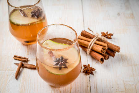Autumn drinks. Mulled wine. Traditional autumn spicy cocktail with pear, cider and chocolate syrup, with cinnamon, anise, brown sugar. On a white wooden table. Copy space Stock Photo