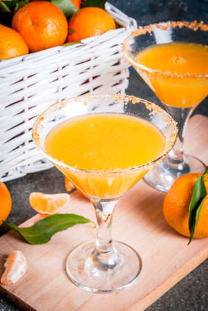 Recipes and ideas of winter fruit cocktails, Tangerine martini margarita with fresh tangerines in basket, on dark background, copy space Stock Photo