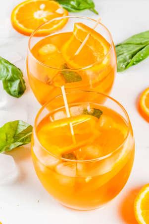 夏は、さわやかなドリンク、レモネード、オレンジとバジルのカクテル。白い大理石のテーブル スペースをコピーします。 写真素材