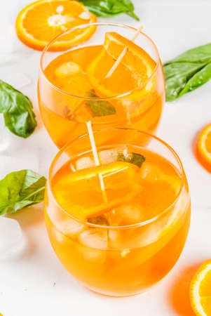 Summer refreshing drink, lemonade, cocktail with orange and basil. On a white marble table, copy space