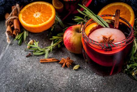 伝統的な冬と秋のドリンク。クリスマスや感謝祭のカクテル。オレンジ、リンゴ、ローズマリー、シナモンとスパイスに暗い石の背景にコピー スペ 写真素材