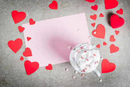 Romantic background, Valentines day. Stone table with blank paper for letter, congratulations, hot chocolate with whipped cream and sweet hearts, decorated with paper red hearts, top view copy space