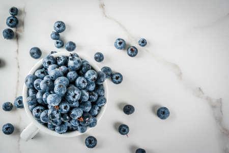 Frische rohe organische Bauernhofblaubeere in der weißen Schale auf weißem Marmorküchenhintergrund, Draufsicht des Kopienraumes