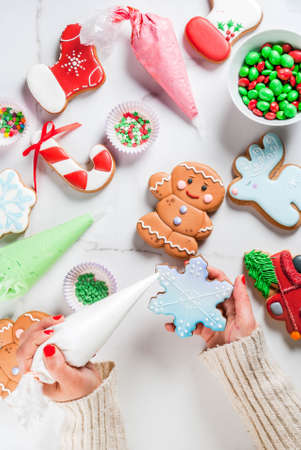 Preparation for Christmas, the girl (hands in the picture) decorates homemade hand-made traditional gingerbread with multicolored sugar icing, biscuits, white marble table. top view copy space