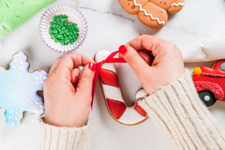 Preparing for Christmas, decorating traditional gingerbread with multicolored sugar icing, white marble table. Girl (hands in picture) knot ribbon bow on candy cane gingerbread, top view copy space Stock Photo