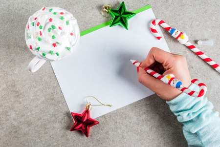 A gray table with a greeting sheet, Christmas decorations, a cup of hot chocolate and pen in form of candy cane. Girl writing, female hand in picture, copy space top view