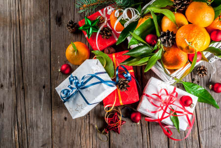 Christmas and New Year concept. Fresh Tangerines with green leaves in a white basket, Christmas decoration and gift boxes, on old rustic wooden table, copy space top view