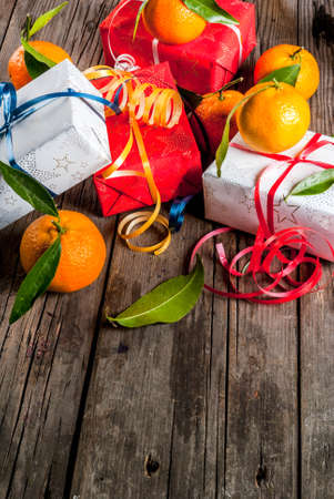 Christmas and New Year concept. Fresh Tangerines with green leaves in a white basket, Christmas decoration and gift boxes, on old rustic wooden table, copy space