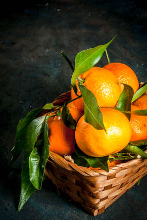 Fresh raw organic Tangerines with green leaves in little basket on dark concrete stone background, copy space Stock Photo