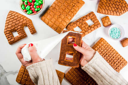 Preparation for Christmas, New Year. Cooking and decoration of traditional advent gingerbread house, female hands in picture, top view, white marble background.