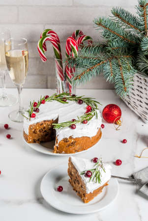 Christmas fruit cake or pudding, decorated with rosemary and cranberry, with christmas decoration, on white marble table, copy space