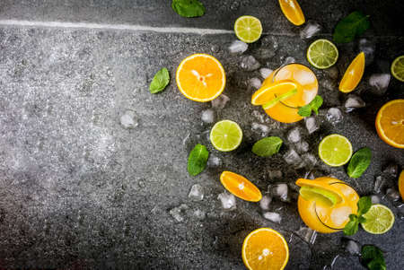 Vitamin summer refreshing drinks. Citrus punch with oranges and lime, with mint sprigs, chilled with ice. On black stone table, with ingredients, copy space top view
