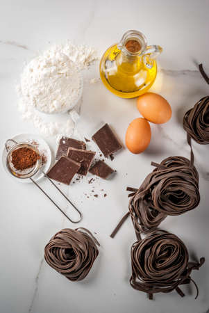 Raw unprepared chocolate pasta noodles, with ingredients for cooking - chocolate, cocoa, flour, eggs,  oil. On a white kitchen marble table. Copy space top view Stock Photo