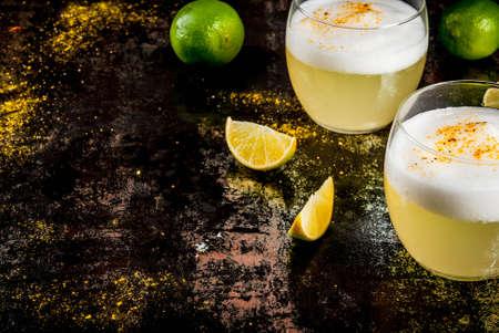 新鮮なライム、さびた黒テーブル、コピー領域の上に、ペルー、メキシコ、チリの伝統的な飲み物のピスコ酸っぱいリキュール 写真素材