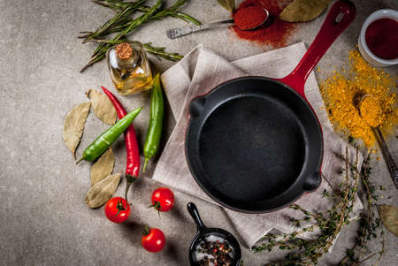 Grey stone culinary background with empty black pan and selection of spices and seasonings, top view copy space