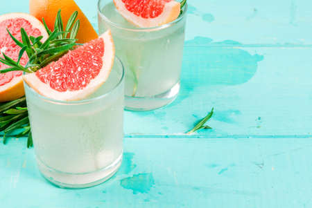 Alcohol drink, Rosemary, Grapefruit & Gin Cocktail, On light blue wooden table background, copy space