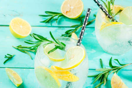 Cold lemonade or alcohol vodka cocktail with lemon and rosemary, on light blue table, copy space 写真素材
