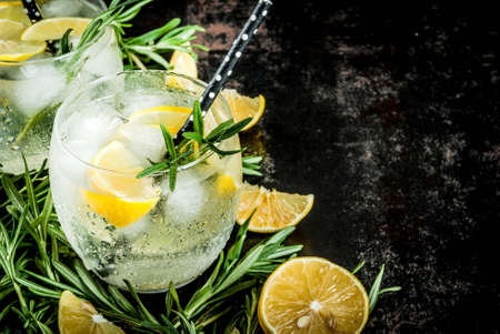 Cold lemonade or alcohol vodka cocktail with lemon and rosemary, On a black rusty metallic background, copy space