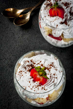 Layered dessert parfait in a glass with strawberries, sponge cake and whipped cream. On a black stone table. Copy space Stock Photo