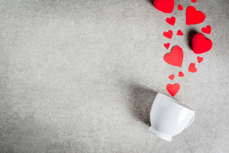 Romantic background, Valentines day. A gray stone table with a cup for coffee or hot chocolate, decorated with paper and plush red hearts, top view flat lay, copy space