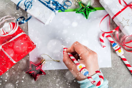 A gray table with a greeting sheet, Christmas decorations, a cup of hot chocolate and pen in form of candy cane. Girl writing, female hand in picture, copy space top view snow effect