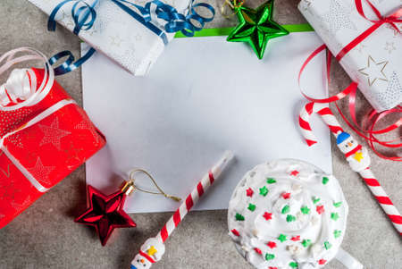 A gray table with a greeting sheet, Christmas decorations, a cup of hot chocolate and pen in form of candy cane. Copy space top view