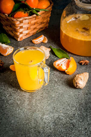 Tangerine Ginger Tea with cinnamon and anise, with ingredients, on dark stone background, copy space Stock Photo