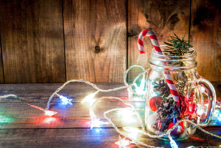 Christmas, New Years concept. Mason Jar with Christmas decorations, fir cones, artificial snow, candy cane and fir branch. On a wooden table background, with a lit garland turned on. Copy space
