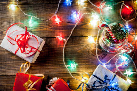 Christmas, New Years concept. Mason Jar with decorations, fir cones, artificial snow, candy cane and fir branch. On a wooden table background, with a lit garland turned on. Copy space top view frame Stock Photo