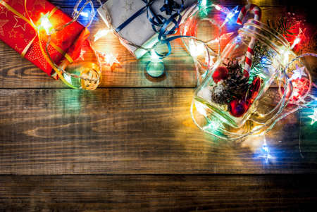 Christmas, New Years concept. Mason Jar with decorations, fir cones, artificial snow, candy cane and fir branch. On a wooden table background, with a lit garland turned on. Copy space top