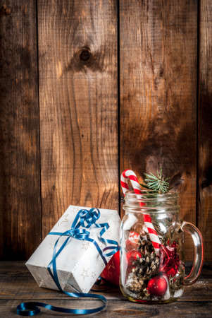 Christmas, New Years concept. Mason Jar with Christmas decorations, fir cones, artificial snow, candy cane and fir branch. On a wooden table background. Copy space