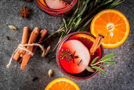 Traditional winter and autumn drinks. Christmas and Thanksgiving Cocktails. Mulled wine with orange, apple, rosemary, cinnamon and spices on a dark stone background, copy space top view Stock Photo